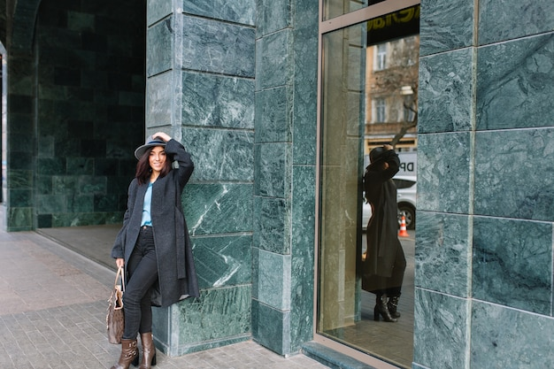 Mulher jovem elegante com casaco cinza, chapéu, andando na rua no centro da cidade. sorrir, emoções verdadeiras, estilo de vida elegante, roupas luxuosas, aparência elegante.