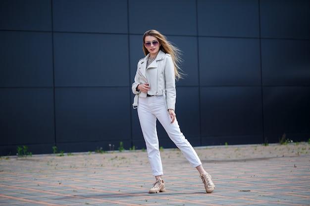 Mulher jovem elegante com longos cabelos loiros de aparência europeia com um sorriso no rosto. menina com uma jaqueta branca e calça jeans branca um dia ensolarado de verão quente no fundo de um edifício cinza