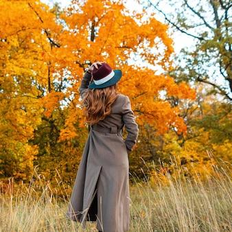 Mulher jovem elegante com roupas elegantes de outono aprecia a paisagem de outono no parque. menina elegante com casaco longo na moda com um chapéu chique está de pé na floresta. vista de trás.