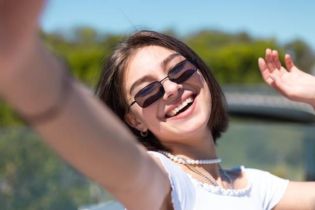 Mulher jovem elegante com top casual recortado branco e óculos de sol tirar foto selfie no celular alegre animado apenas vibrações positivas