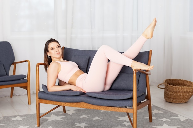 Mulher jovem elegante com um macacão esportivo rosa posando em um pequeno sofá cinza