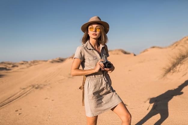 Mulher jovem elegante com vestido cáqui caminhando pelo deserto, viajando pela áfrica em um safári, usando chapéu e mochila, tirando foto com uma câmera vintage