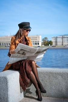 Mulher jovem elegante de etnia caucasiana lê jornal fresco em óculos de sol e boné preto bonito.
