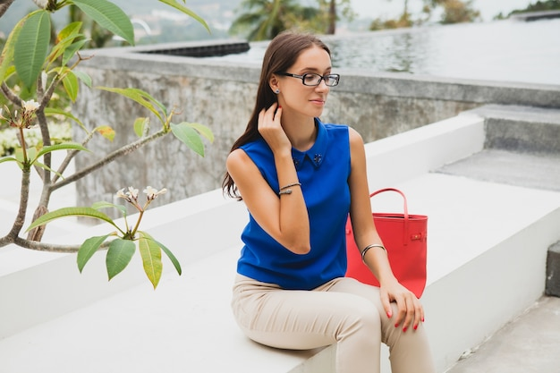 Mulher jovem elegante e bonita, tendência da moda de verão, blusa azul, bolsa vermelha, óculos, resort em uma vila tropical, férias, namoradeira