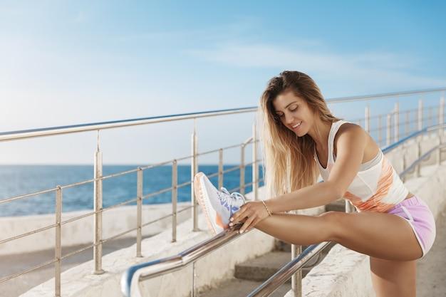 Mulher jovem, elegante e saudável, ativa e atlética fazendo exercícios matinais perto do mar, correndo ao longo do cais