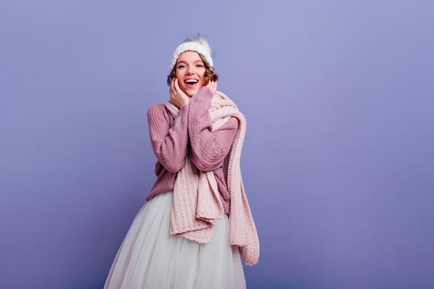 Mulher jovem elegante em acessórios de inverno da moda posando sorrindo adorável garota no suéter em pé na parede roxa.
