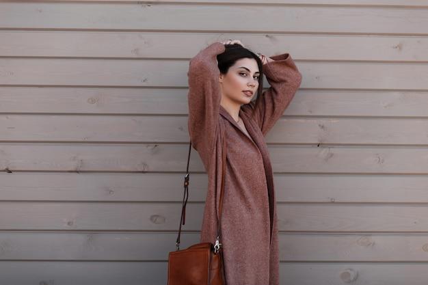 Mulher jovem elegante em elegante casaco na moda elegante com bolsa de couro marrom na moda posando perto de uma parede de madeira na cidade. linda garota moderna com roupas de primavera fica perto de um prédio vintage