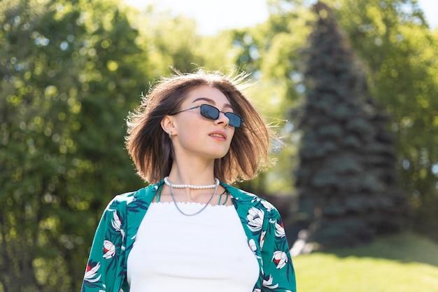 Mulher jovem elegante em jeans e camisa verde casual em dia de sol, posando na grama do parque