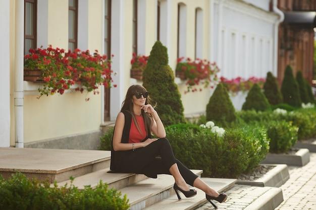 Mulher jovem elegante em óculos de sol da moda e blusa vermelha, sentado na escada, na rua da cidade em um dia ensolarado de verão.