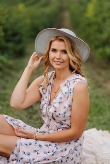 Mulher jovem elegante em rosa vintage vestido azul e chapéu posando em campo verde