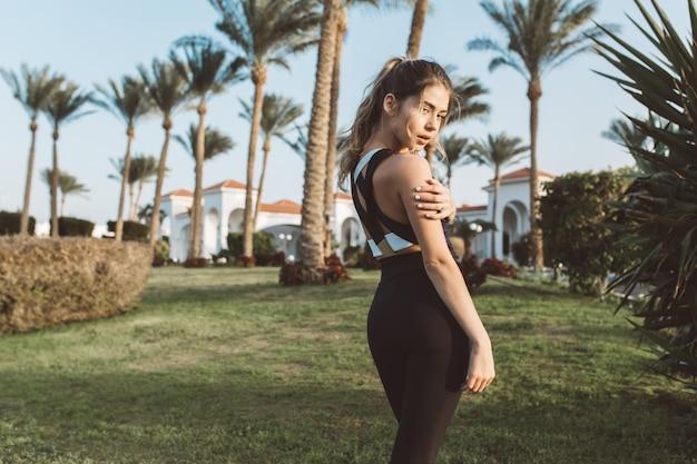 Mulher jovem elegante em roupas esportivas, com cabelo longo encaracolado andando na grama em uma cidade tropical. olhando, estacionar com palmeiras, treinamento, ginástica, fitness