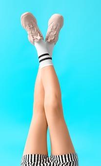 Mulher jovem elegante em sapatos e meias na cor de fundo