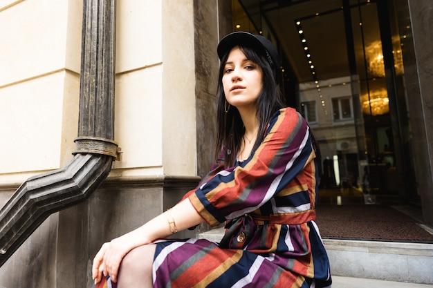 Mulher jovem elegante em um vestido listrado multi colorido e chapéu preto, sentado nos degraus do hotel