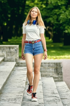 Mulher jovem elegante está andando nas escadas do pavilhão do jardim em um parque público.