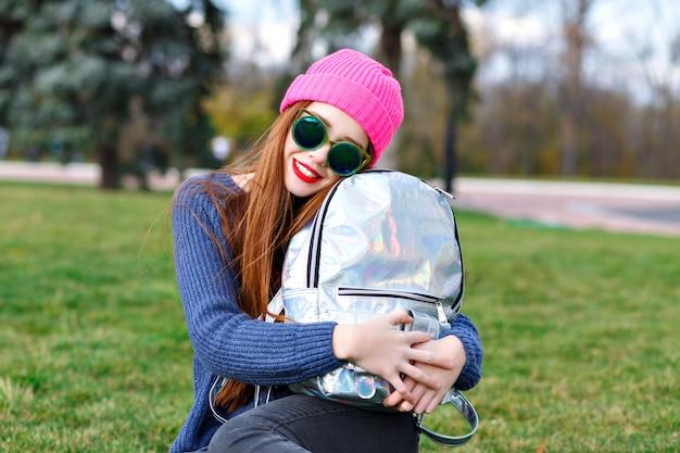 Mulher jovem elegante hippie se divertindo ao ar livre, usando óculos escuros e feno de suéter aconchegante, viajar com mochila, emoções surpresas, estilo de cidade de rua.
