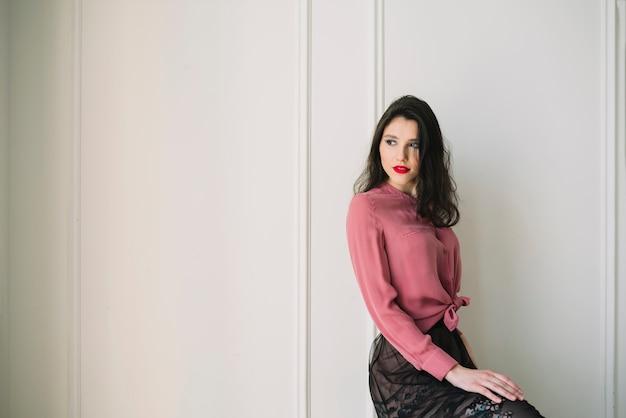 Mulher jovem elegante na blusa e saia no quarto