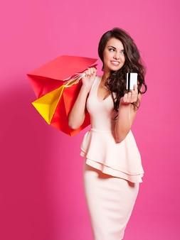 Mulher jovem elegante posando com cartão de crédito e sacolas de compras