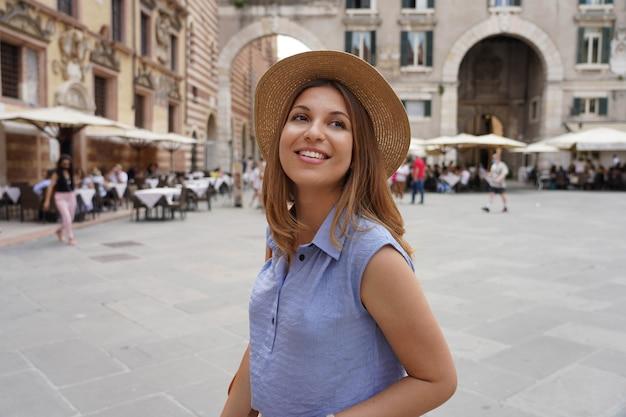 Mulher jovem elegante que visita a cidade de verona, na itália, em sua viagem cultural pela europa.