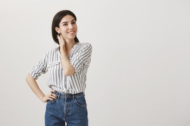 Mulher jovem elegante tocando o pescoço e sorrindo