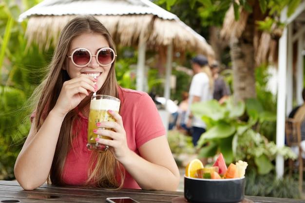 Mulher jovem elegante usando óculos escuros redondos, sentado no balcão do bar e bebericando o shake de frutas com canudo, relaxando e aproveitando o dia de sol durante as férias no quente país exótico.