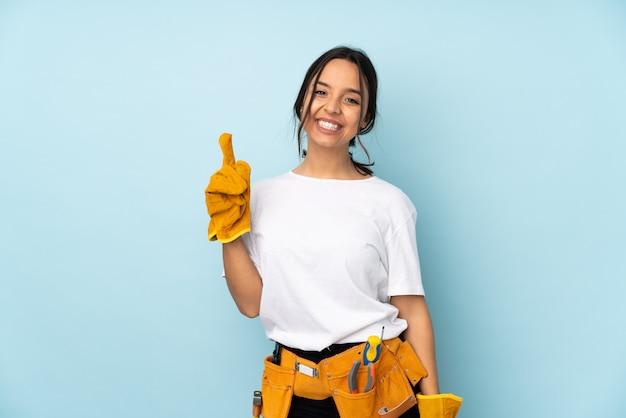Mulher jovem eletricista isolada na parede azul, mostrando e levantando um dedo em sinal dos melhores