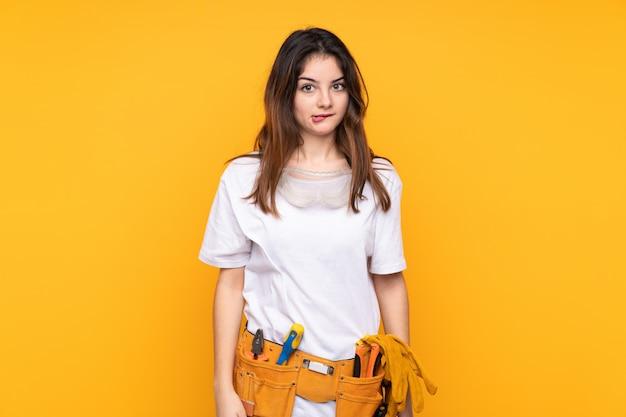Mulher jovem eletricista isolada sobre parede amarela, tendo dúvidas e com a expressão do rosto confuso