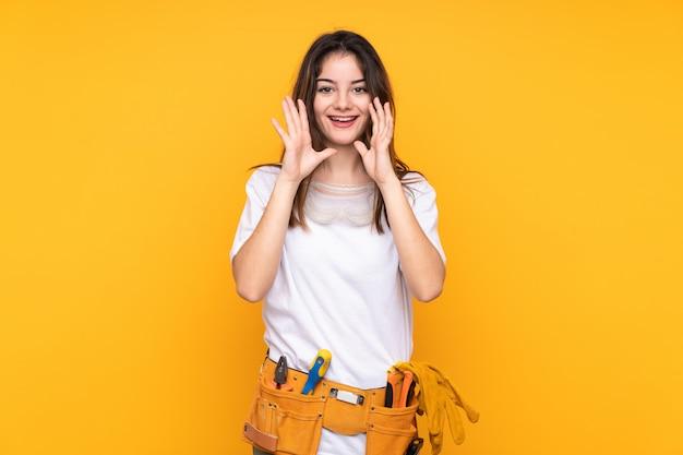Mulher jovem eletricista na parede amarela gritando com a boca aberta
