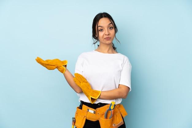 Mulher jovem eletricista na parede azul infeliz e confusa