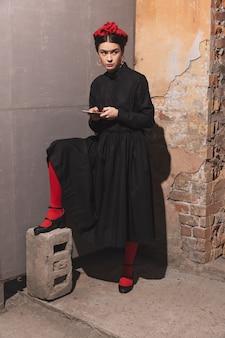 Mulher jovem em ação artística refazendo as maiores pinturas e seus artistas em uma parede antiquada.