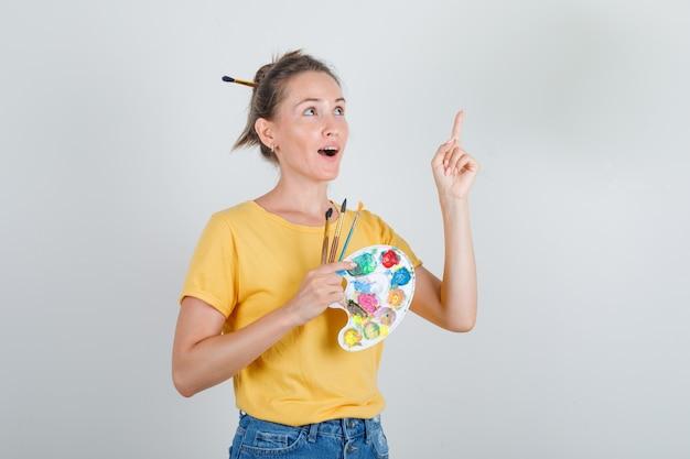 Mulher jovem em amarelo apontando o dedo com ferramentas de arte