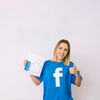 Mulher jovem, em, azul, t-shirt, segurando, semelhante, ícone, mostrando, thumbup, sinal