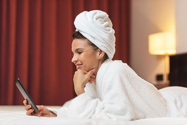 Mulher jovem, em, bathrobe, mentindo, em, quarto hotel, usando, telefone móvel, relaxado, após, fazendo exame um banho