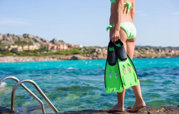 Mulher jovem, em, biquíni, segurando, engrenagem snorkeling