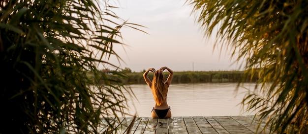 Mulher jovem, em, biquíni, sentando, ligado, um, cais, em, a, lago