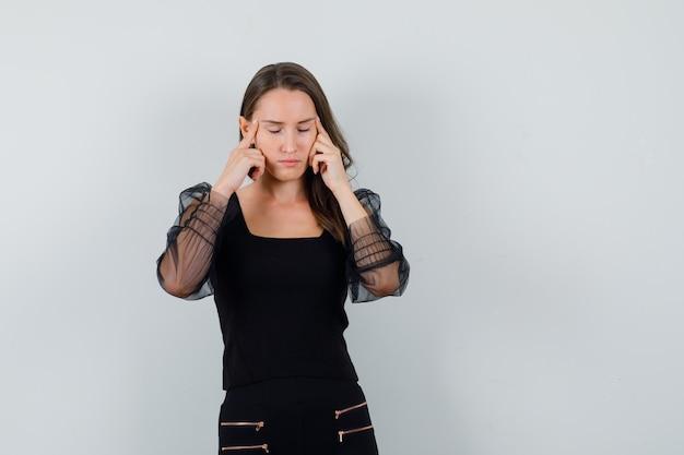 Mulher jovem em blusa preta e calça preta esfregando as têmporas e parecendo exausta, vista frontal.