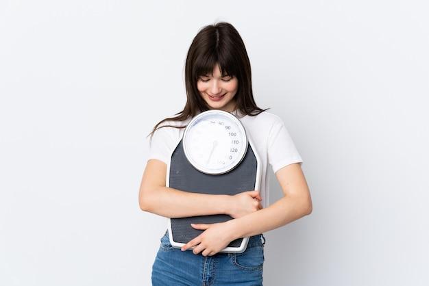 Mulher jovem em branco isolado com balança