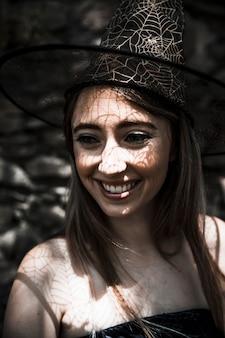 Mulher jovem, em, bruxa, chapéu, sorrindo