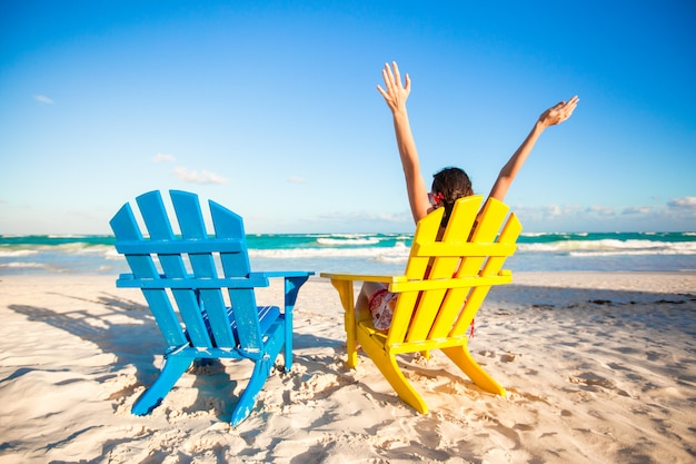 Mulher jovem, em, cadeira praia, levantado, dela, mãos cima