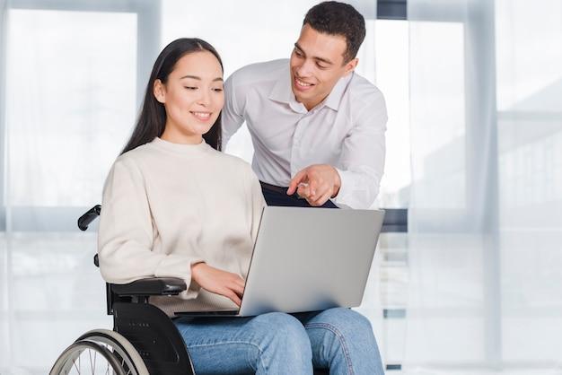 Mulher jovem, em, cadeira rodas, trabalhando, com, um, colega masculina