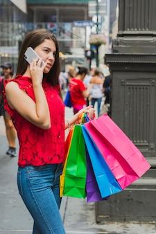 Mulher jovem, em, calças jeans, telefonando, com, bolsas para compras