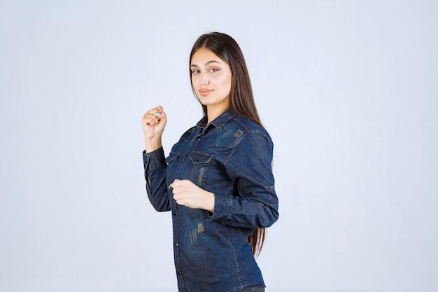 Mulher jovem em camisa jeans correndo de um lugar