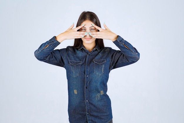 Mulher jovem em camisa jeans olhando por entre os dedos