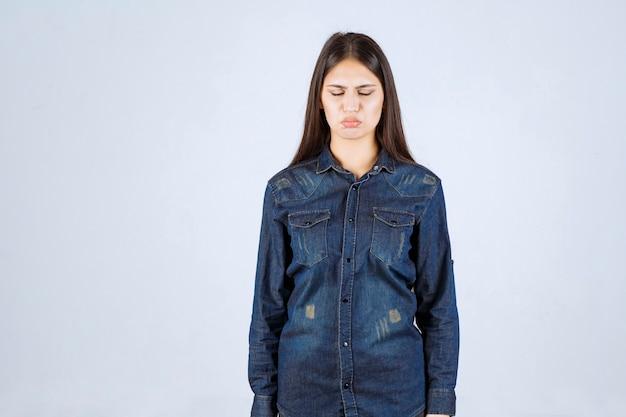 Mulher jovem em camisa jeans parece exausta e com sono