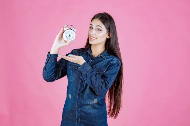 Mulher jovem em camisa jeans segurando e promovendo um despertador