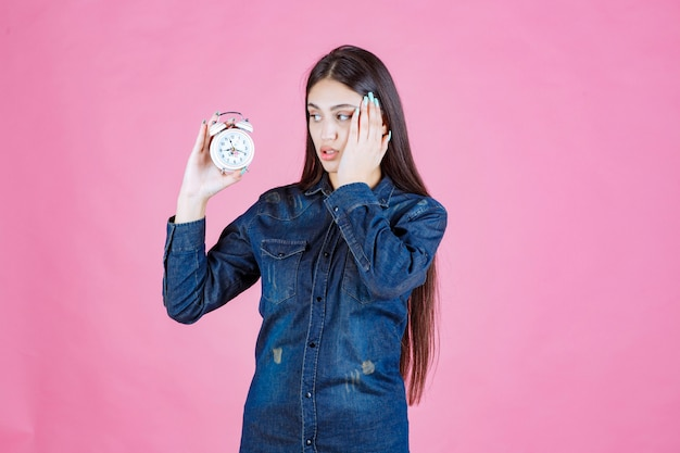 Mulher jovem em camisa jeans segurando o despertador e cobrindo a orelha por causa do anel