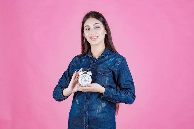 Mulher jovem em camisa jeans segurando o despertador entre as mãos