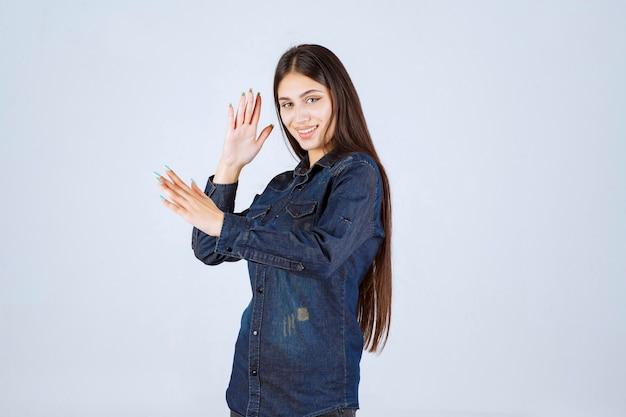 Mulher jovem em camisa jeans sorrindo e fazendo careta