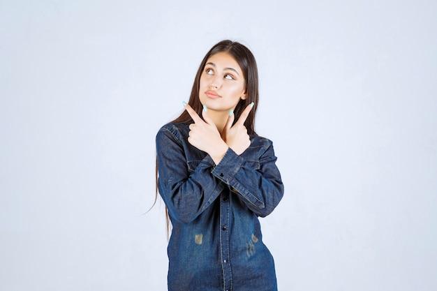 Mulher jovem em camisa jeans tentando prevenir e impedir algo