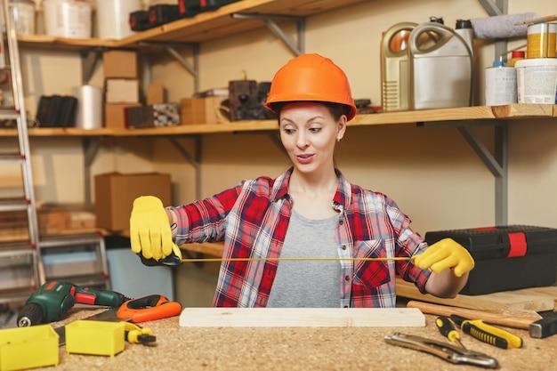 Mulher jovem em camisa xadrez, camiseta cinza, luvas amarelas, capacete protetor medindo comprimento de pedaço de madeira com fita métrica, trabalhando em oficina de carpintaria em mesa de madeira lugar com ferramentas diferentes