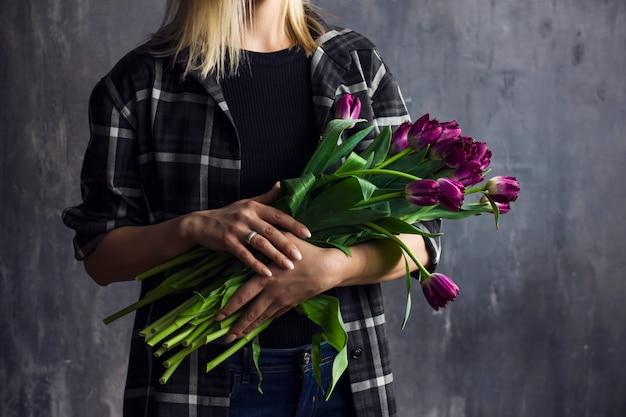 Mulher jovem, em, camisa xadrez, segurando, buquet, de, roxo, terry, tulips, fundo escuro